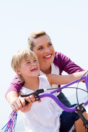 pretty mom and daughter riding bike photo