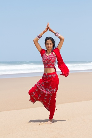 traditional indian woman doing yoga on beach photo