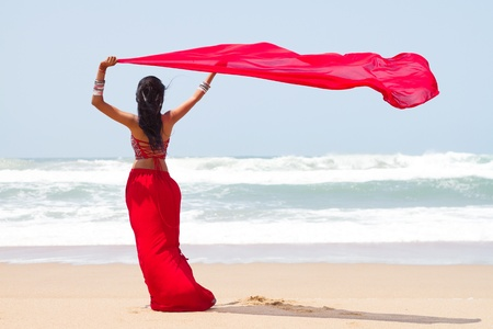modern woman with scarf blowing in ocean breeze