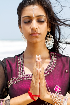 indian woman praying on beach photo