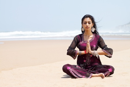 indian woman meditating on beach photo
