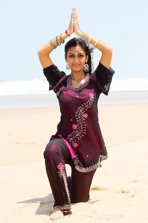 femme indienne faisant yoga sur la plage