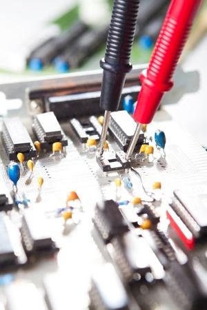 electronics parts: Multimeter examining a circuit board