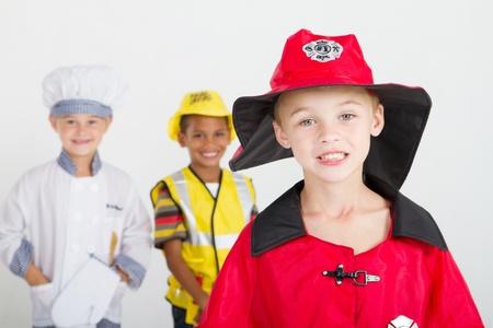 r�le: petit gar�on comme pompier, arri�re-plan est kids comme chef et construction travailleur Banque d'images
