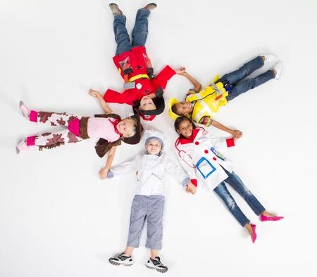group of kids in various uniforms lying on floor photo