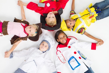 group of kids in various uniforms lying on floor Stock Photo - 9169038
