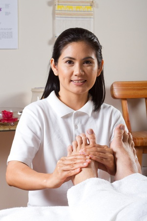 asian woman giving professional foot massage (spa)