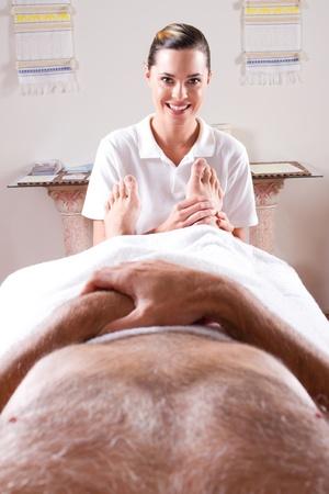 professional masseuse giving foot massage to male customer photo