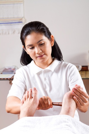 masseuse: asian masseuse giving foot massage  Stock Photo