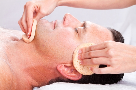 salon treatment: middle age man receiving facial massage in beauty spa Stock Photo