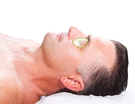 middle aged man with cucumber facial mask in spa photo