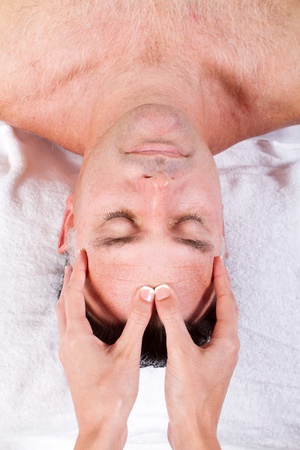 middle aged man receiving facial massage photo