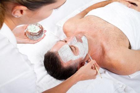 salon treatment: man facial mask in luxury beauty spa
