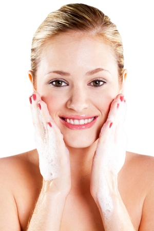 Beautiful caucasian woman washing her face with foam photo