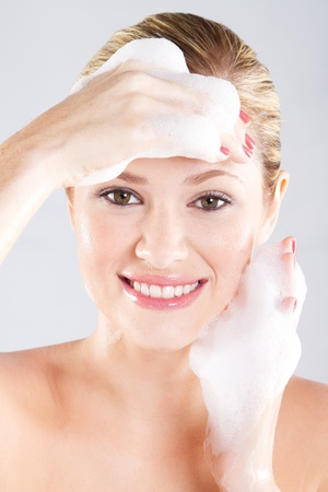Beautiful caucasian woman washing her face with foam photo