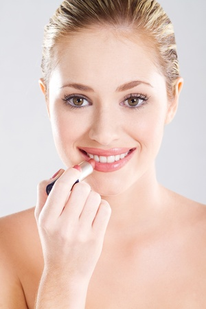 cleaness: happy young beautiful woman applying lipstick