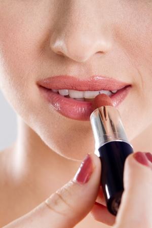 closeup of young woman applying lipstick photo