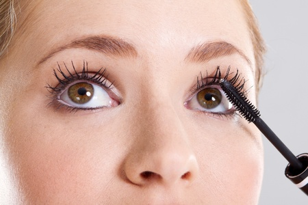 cleaness: happy young pretty woman applying mascara on her eyelashes