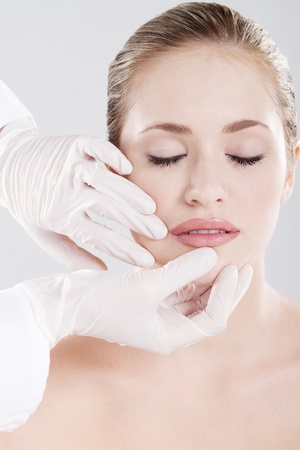 doctor checking womans lips before cosmetic surgery photo