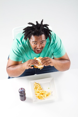 overhead view of fat african american man eating hamburger photo