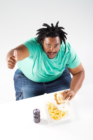 fat african american man giving thumb up while eating hamburger photo
