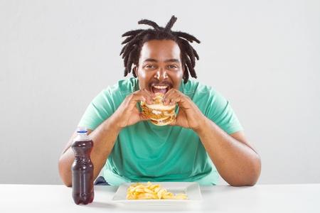 happy fat african american man eating a hamburger photo
