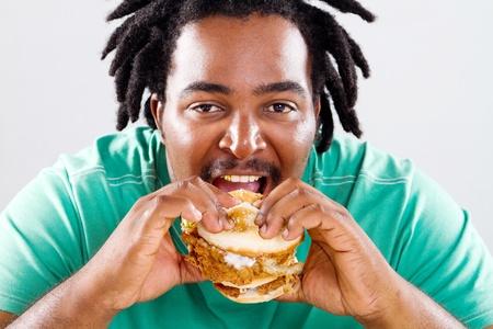 hombre comiendo: feliz fat man afroamericano una hamburguesa Foto de archivo