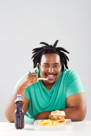 fat african american man eating chips photo