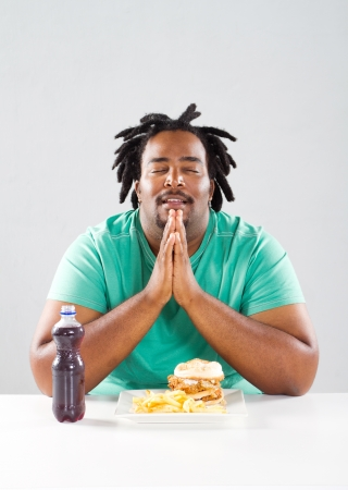 overweight african american man pray before eating a meal photo