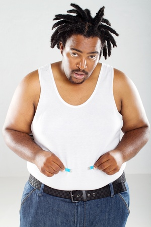 unhappy man: overweight african man with measuring tape