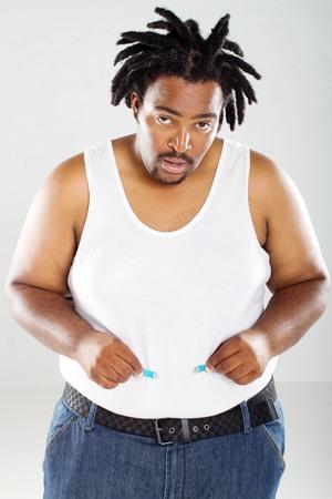 persona triste: sobrepeso a hombre africano con cintas m�tricas Foto de archivo