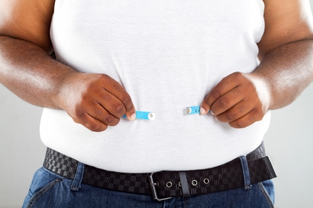 obesity: fat african man with measuring tape