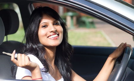 beautiful indian girl face: young woman driving a car