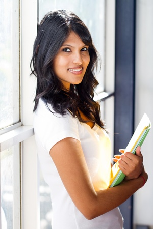 pretty university student standing by glass window photo