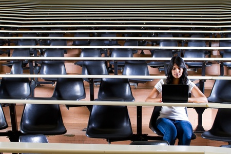 college classroom: female college student alone in university lecture hall