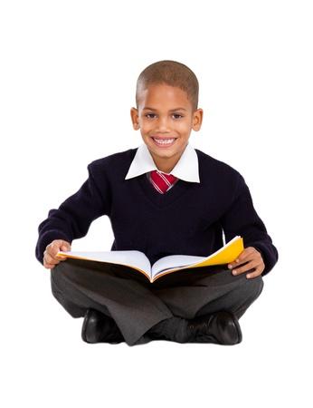 escuela primaria: escolar primaria sentado en el suelo y la lectura Foto de archivo