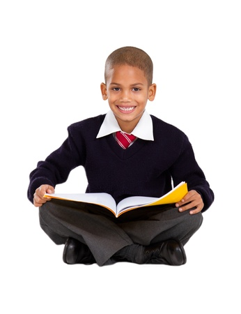 primary schoolboy sitting on floor and reading photo