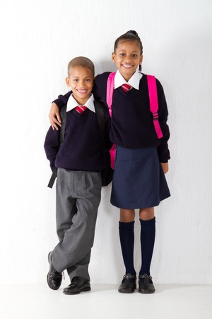 uniform student: two primary pupils standing against classroom wall