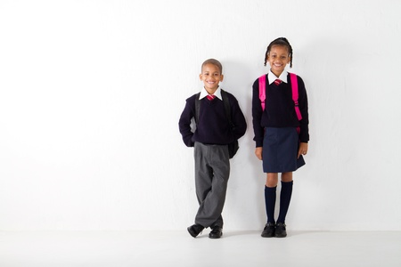 two primary students standing against wall