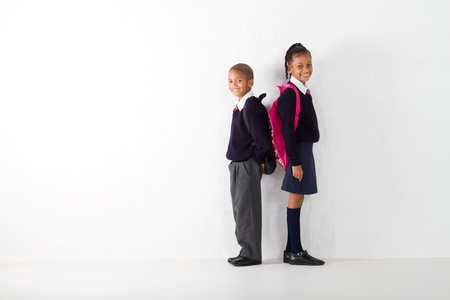two elementary students standing against wall photo