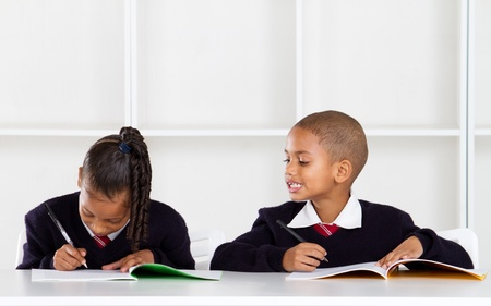 cheat: cute elementary schoolboy peeking on classmates answer Stock Photo