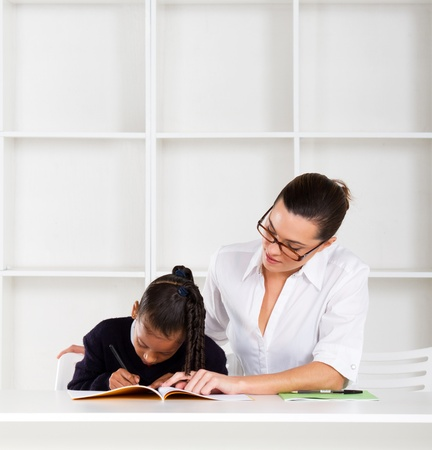 caring tutor helping schoolgirl with homework photo