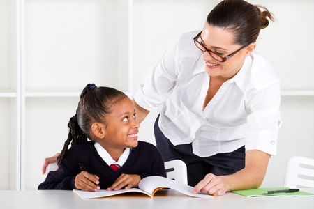 tutoring: primary school teacher and pupil in classroom