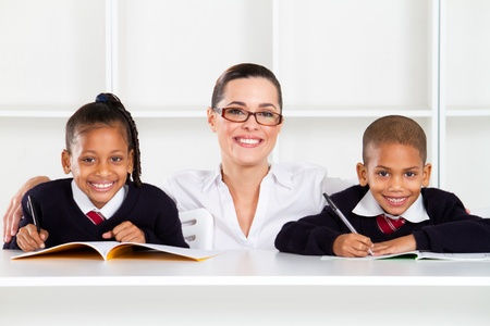 caring primary teacher and students in classroom photo