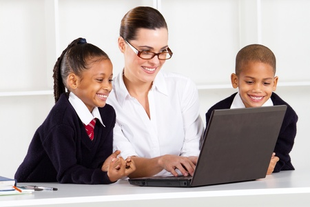 elementary teacher teaching computer class to students photo