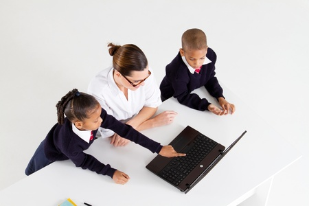 overhead view of primary teacher and students using laptop photo