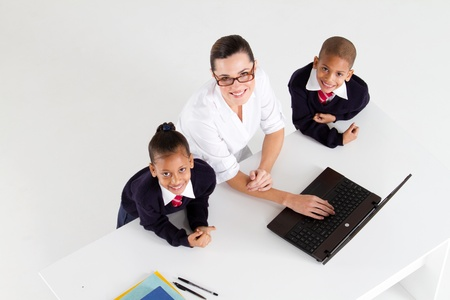 overhead view of elementary teacher and student in front of a laptop Stock Photo - 10747043