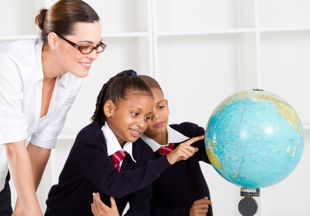 uniform student: primary teacher and students looking at globe in classroom