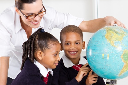 elementary geography teacher and students looking at globe in classroom photo