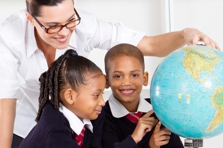tutor: profesor de geograf�a de primaria y estudiantes que buscan en el mundo en el aula Foto de archivo